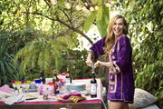 Jacqui Getty poised amid wineglasses, cloth napkins, and a tablecloth atop an outdoor table