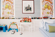 Toys and a white table and chairs in a colorful playroom
