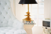 A gold lamp with a black shade next to a white tufted armchair