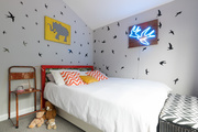 A kid's bedroom with gray walls and wall decals.