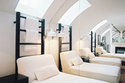 A skylight and a wall of mirrors in a neutral lounge space