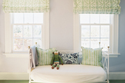 A green pouf and a daybed in a room with patterned roman shades