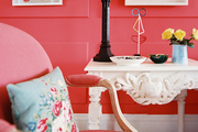 A white carved-wood table and a pink upholstered chair against red walls