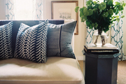 Blue patterned pillows on a white settee beside a gray end table