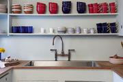 Open shelving with bright tableware in the kitchen of a Hamptons getaway