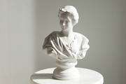 A white bust on a marble and brass pedestal.