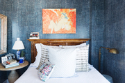 A bedroom with blue and white wallpaper.