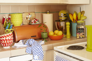 An orange bread box and assorted colorful kitchen gadgets sit on a counter.