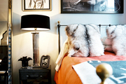 Fur pillows and orange bedding on an iron bed