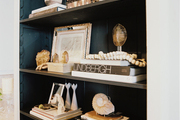 A bookshelf styled with black, white, and tan decorative accessories
