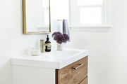 A bathroom sink with wooden drawers and gold accent pieces.