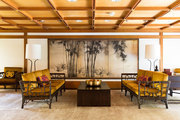 Bamboo-framed gold sofas stand in front of mounted Japanese screens