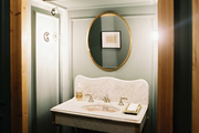 An oval gold mirror above a marble sink