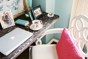 A white loop chair and a weathered desktop in a blue office nook