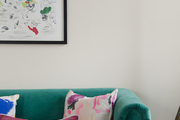 A green velvet sofa with colorful pillows