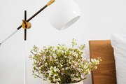 A detail of a nightstand with a midcentury style while lamp, a white dish, and a vase with flowers.