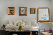 White sofa below paintings in gold frames.