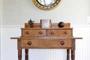 Round vintage mirror above wooded table with drawers.