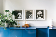 A cobalt blue credenza with three illustrations hanging above.