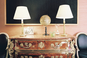 A black-and-white piece of contemporary art hung above an ornate antique wooden chest and a pair of chairs