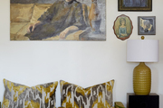 A mustard-colored velvet daybed with printed throw pillows beneath a gallery wall of paintings.