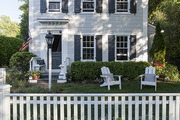 A house in Sag Harbor with dark blue window shutters and a white picket fence