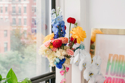 A vase of flowers is placed in front of a window.