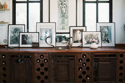 A wooden sideboard decorated with framed art