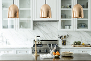 A trio of hammered-copper pendant lamps above a custom wood island in a whitewashed kitchen