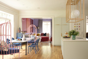 Eclectic open plan kitchen with pink dining chairs and modern pendant lighting.