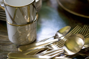 Flatware and teacups on a marble surface