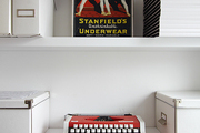 A vintage advertisement and red typewriter displayed on all white shelving