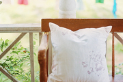 A colorful clothesline and a vintage floral pillow add charm to a country style wrap-around porch.