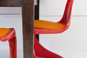 A red midcentury dining chair with an orange seat cushion