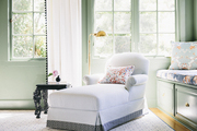 A white chaise longue trimmed with a Greek key pattern in a bedroom with floral accents
