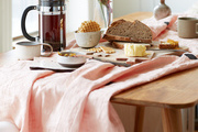 A breakfast spread over a wooden table with a pink table cloth.
