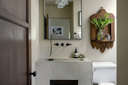 Modern light fixture hanging above concrete sink.