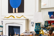A painting above a sculpture-topped fireplace mantel in a contemporary living space