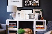 Framed art and a glass lamp atop a white desk surrounded by upholstered seating