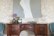 A traditional wooden console table in front of a wall with gold wall treatment and a modern gray artwork.