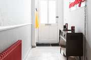 A contemporary entryway with white walls and red accents.