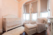 Tonal nursery room with rocking chair and fur area rug.