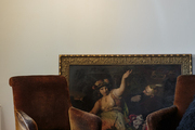 Velvet armchairs and gilded artwork in a guest room