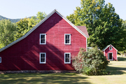 A red barn surrounded by lush greenery