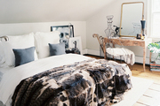 A bed dressed with white linens and a fur throw