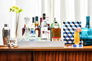 A bar station with an array of liquors decorates a room
