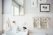 White tile and gray walls in a bathroom with a pedestal sink