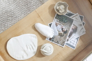 Family photos and ceramic baby foot and hand prints on a wooden table.