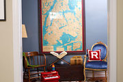 A large vintage map hangs over a cowhide rug