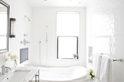 Small tiled floor and white walls surrounding a marble bath.